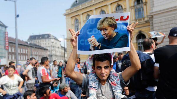 Мигрант с фотографией Ангелы Меркель в Будапеште. Архивное фото