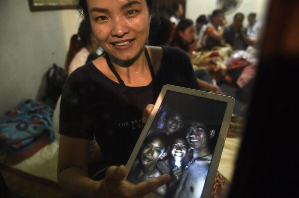 Родственница показывает фотографию найденных в пещере игроков детской футбольной команды и их тренера в Таиланде