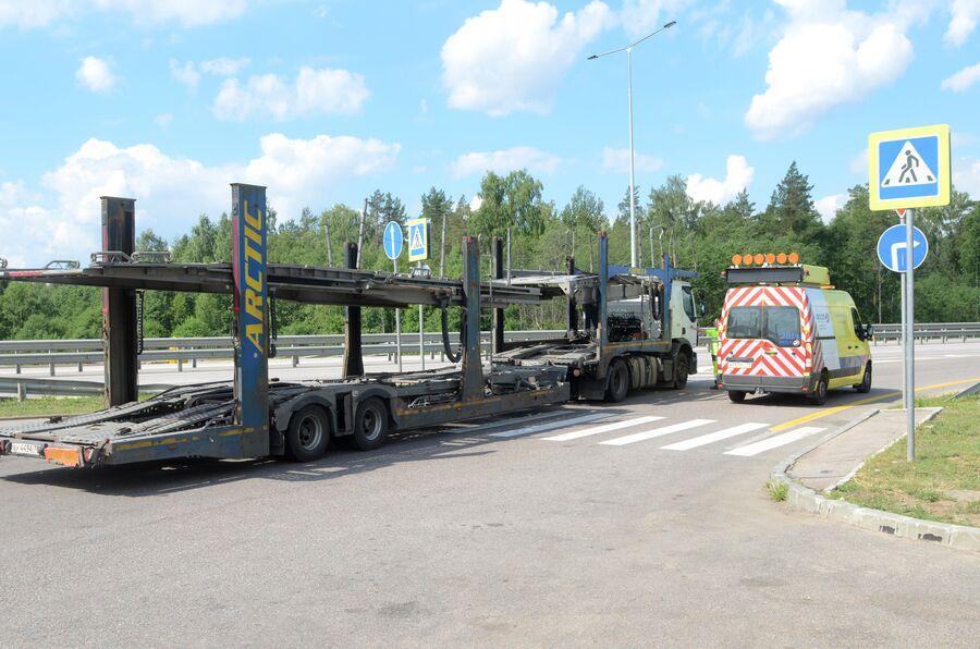 Грузовой автомобиль и машина Службы аварийных комиссаров на площадке отдыха трассы М-11