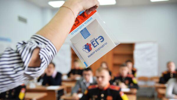 Преподаватель демонстрирует пакет и компакт-диск с заданиями перед началом единого государственного экзамена по базовой математике в Лицее №88 в Екатеринбурге. Архивное фото