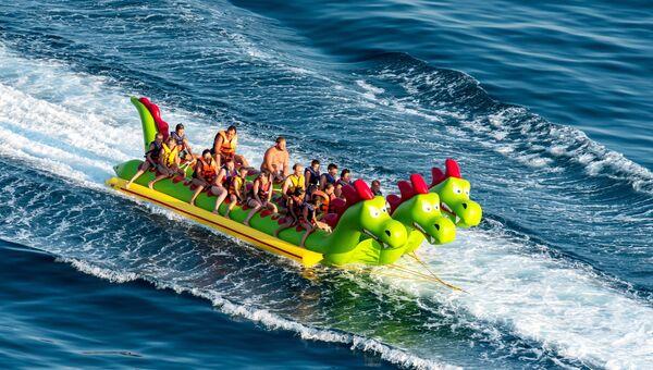Отдыхающие катаются на банане за катером в поселке Рыбачье в Крыму