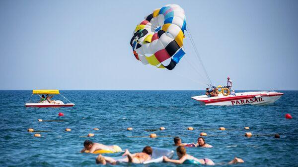 Отдыхающие купаются и катаются на парашюте в Судаке