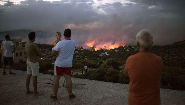 Люди наблюдают за лесным пожаром в городе Рафина, недалеко от Афин. 23 июля 2018 года