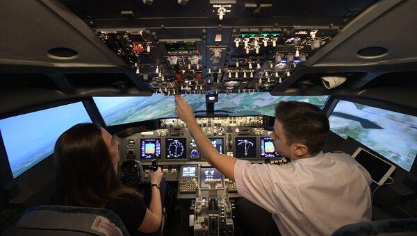 Девушка с инструктором в кабине авиатренажёра, моделирующего кабину самолета Boeing 737 NG