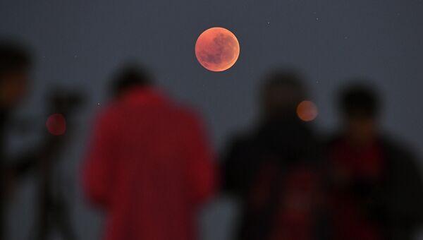 Люди на фоне Луны. Архивное фото