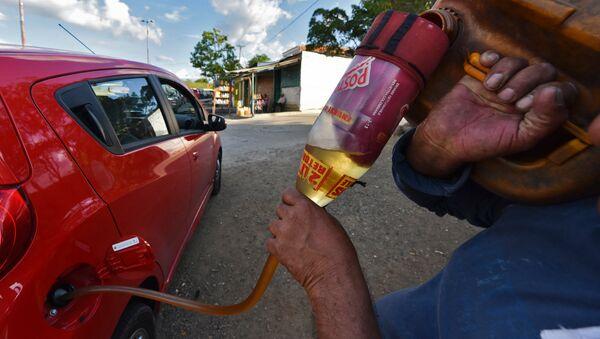 Заправка автомобиля бензином на границе Венесуэлы и Колумбии. Архивное фото