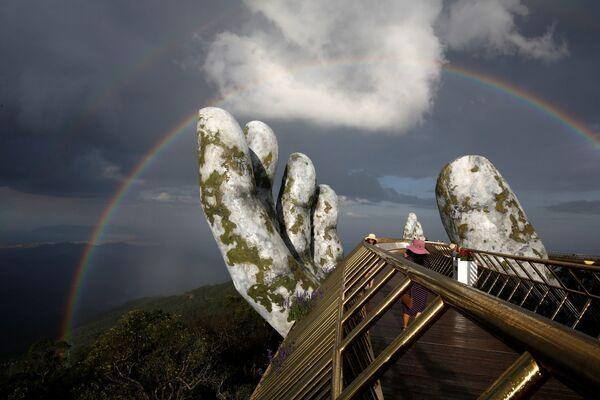 Золотой мост во Вьетнаме на фоне радуги.