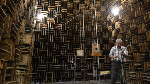 Сотрудник института настраивает оборудование в большой заглушенной камере