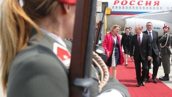 Президент РФ Владимир Путин и министр европейских, интеграционных и иностранных дел Австрии Карин Кнайсль в аэропорту Швехат в Вене. Архивное фото