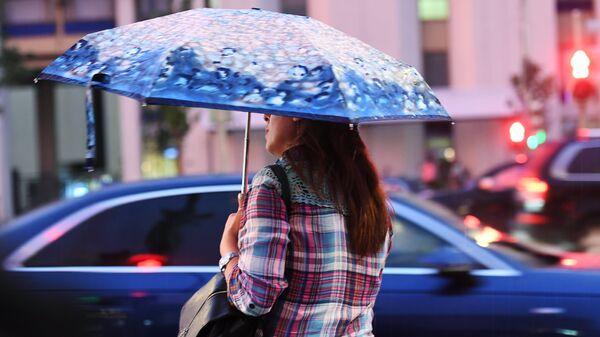 Женщина переходит дорогу во время дождя в Москве. Архивное фото