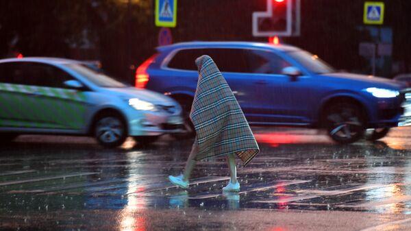 Прохожий переходит дорогу во время дождя в Москве