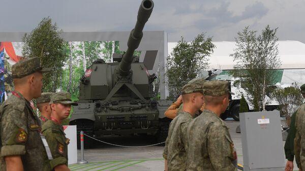 Военнослужащие на фоне самоходной артиллерийской установки Коалиция-СВ на форуме Армия-2018 в Кубинке