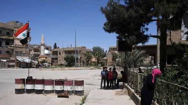 Жители на улице в сирийском городе Дейр-эз-Зор