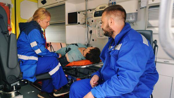 Врачи скорой медицинской помощи оказывают первую помощь пациенту