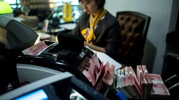 Сотрудница в отделении банка в Шанхае. Архивное фото