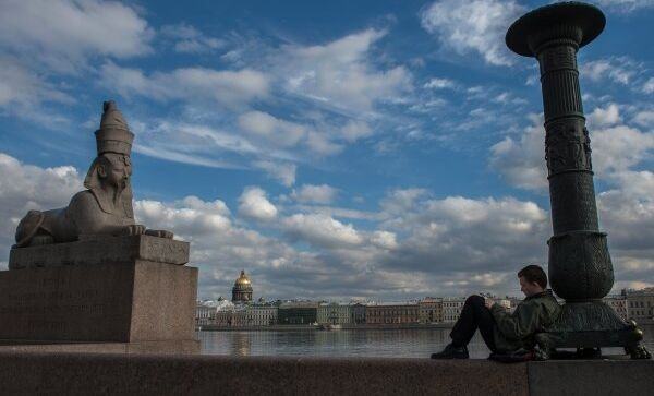 Молодой человек рисует на Университетской набережной в Санкт-Петербурге