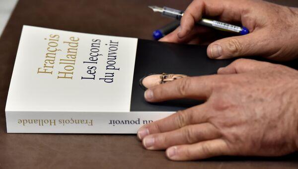 Книга о презендентском сроке Франсуа Олланда в его руках