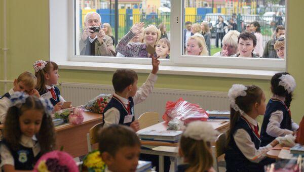 Родители в окне средней общеобразовательной школы во время первого занятия