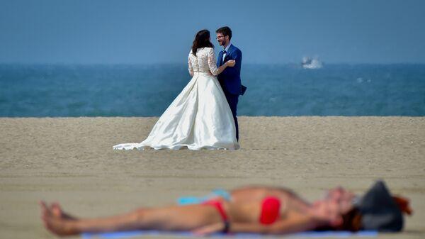Молодожены позируют на пляже во время 44-го кинофестиваля американского кино в Довиле