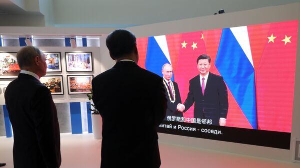 Президент РФ Владимир Путин и председатель Китайской Народной Республики Си Цзиньпин во время осмотра выставки в рамках IV Восточного экономического форума