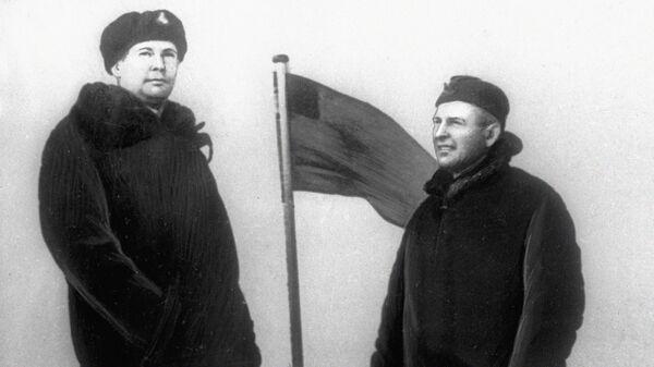Командир атомной подводной лодки Ленинский комсомол Лев Жильцов и замполит А. Штурманов у флага, установленного ими близ Северного Полюса