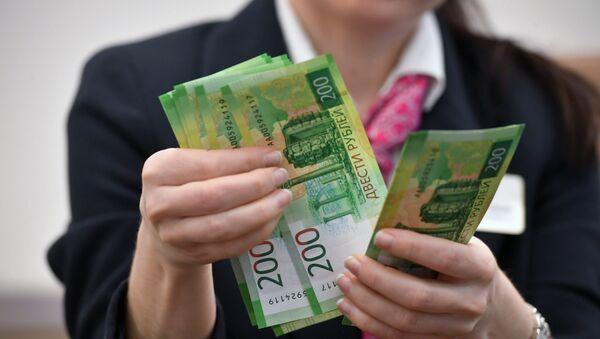 Сотрудница банка проводит денежные операции с новыми купюрами номиналом 200 и 2000 рублей. Архивное фото