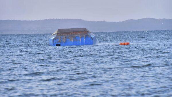 Спасатели осматривают корпус парома, который опрокинулся на озере Виктория в Танзании. 21 сентября 2018