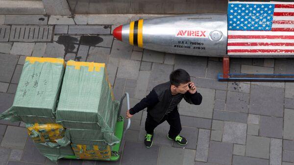 Мужчина с тележкой возле скамейки в виде ракеты с флагом США рядом с магазином в Пекине