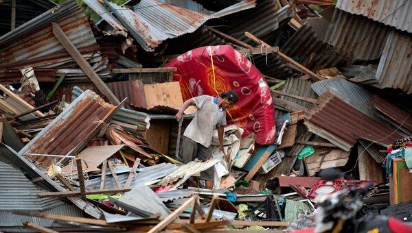 Мужчина ищет свои вещи среди обломков разрушенного дома в городе Палу на острове Сулавеси, где прошло сильное землетрясение и цунами. 29 сентября 2018