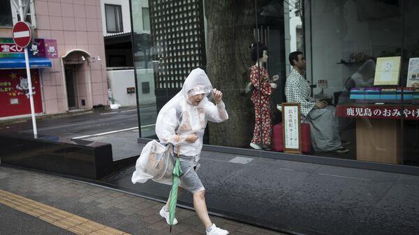 Житель города Кагашима в Японии спасается от погоды испортившейся в связи с приходом тайфуна Трами. 30 сентября 2018