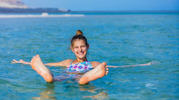 Девушка плавает в Мертвом море, Израиль