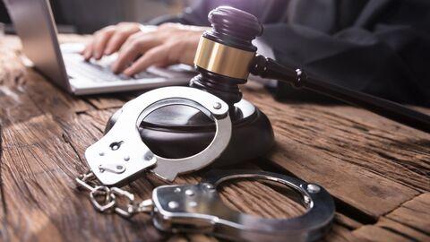 Молоток и наручники на столе у судьи