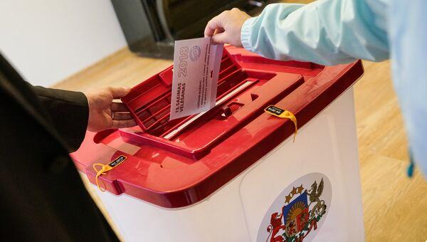 Избиратель опускает бюллетень в урну на избирательном участке во время парламентских выборов в 13-й Сейм Латвии. 6 октября 2018