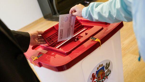 Избиратель опускает бюллетень в урну во время парламентских выборов в Латвии