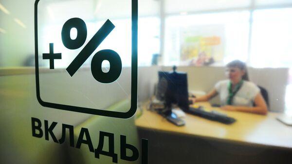 Сотрудница банка за работой в отделении Сбербанка России. Архивное фото