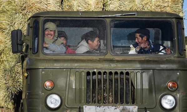 Работники в кабине грузовика во время сбора сена в монгольской степи