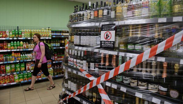 Стеклянные бутылки с алкоголем на витрине магазина в Волгограде
