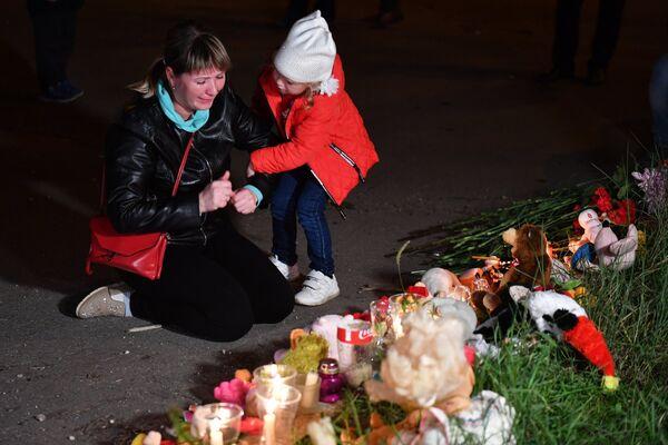 Женщина у народного мемориала на улице в Керчи, где в Керченском политехническом колледже произошли взрыв и стрельба