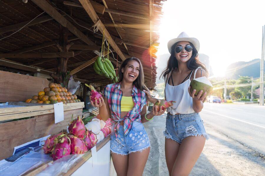 Девушки покупают экзотические фрукты