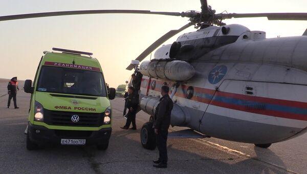 Карета скорой помощи с пострадавшими при нападении на Керченский политехнический колледж у вертолета Ми-8 МЧС России, который транспортирует пострадавших в Симферополь