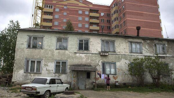 Ветхий жилой дом на фоне новостройки