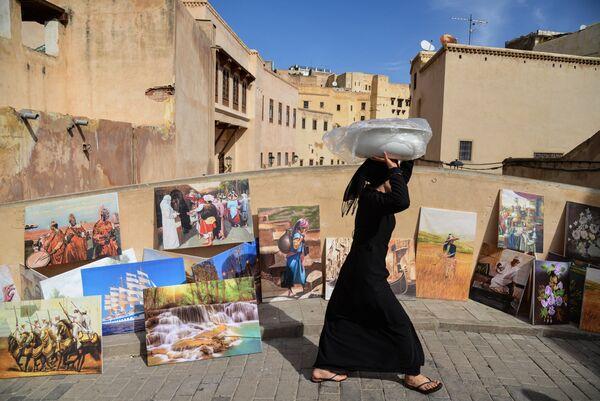Женщина идет по мосту в городе Фес, Марокко