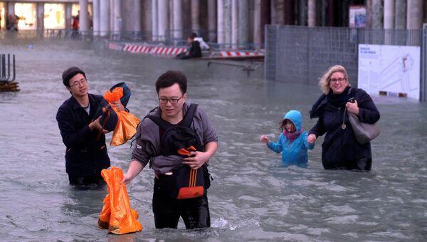Туристы на затопленной площади Святого Марка во время сезонного половодья в Венеции, Италия. 29 октября 2018 года