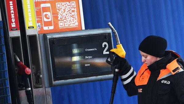 Рабочая у заправочной колонки на автозаправочной станции в Москве. Архивное фото