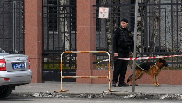 Сотрудник полиции с собакой у входа в здание управления ФСБ по Архангельской области, где произошел взрыв