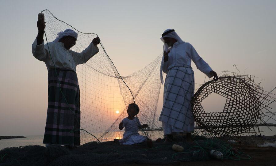 Мужчины обучают ребенка ремеслам во время фестиваля парусного спорта  у побережья Далмы, ОАЭ
