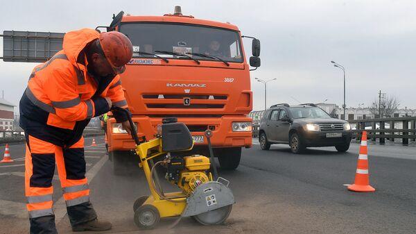 Рабочие ремонтируют участок дороги