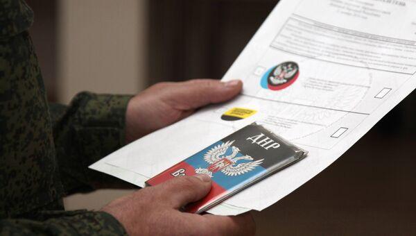 Военнослужащий Донецкой Народной Республики держит воинский билет и избирательные листы для голосования на выборах главы ДНР