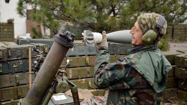 Украинский военнослужащий заряжает миномет