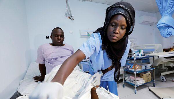 Фельдшер в госпитале осматривает человека, получившего ранения во взрыва около отеля в Могадишо, Сомали. 10 ноября 2018